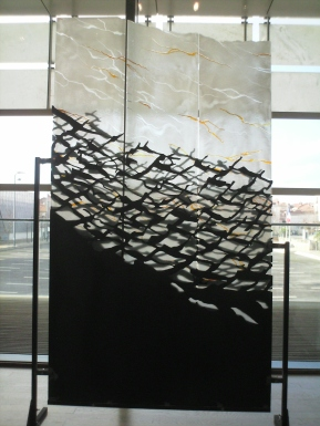 Glass screen with patterns in black, white and gold, resembling surf and seagulls.