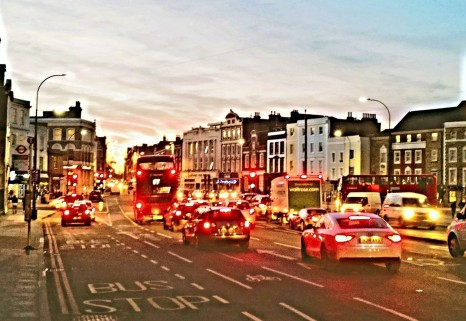 Busy junction in the dusk, with red and yellow lamps of cars and buses glaring.