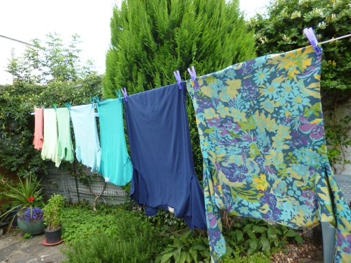 Line of washing outdoors, very colourful, above greenery and flower-pot.