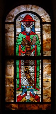 Colourful ancient glass window, prophet in red hat, red shoes, green cloak.