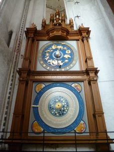 Large astronomical clock with two blue and golden dials in wooden frame.